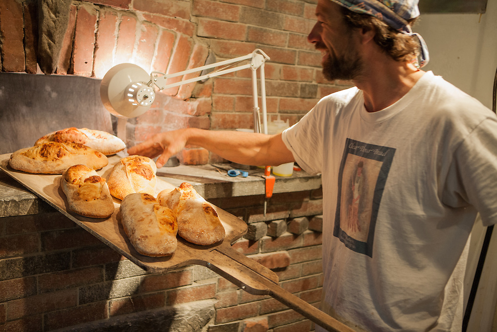 Jamestown, RI - 7 May 2007. Andrea Colognese of The Village Hearth Bakery and Cafe, taking  loaves of Asiago cheese bread out of the oven.