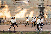 A Mexican mariachi band dressed in traditional charro costume walk down a road November 5, 2013 in Oaxaca, Mexico.