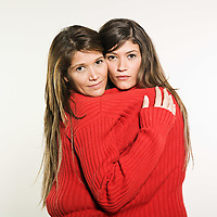 studio shot portrait on isolated background of two sisters twin women friends holding in arms each other