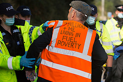 Ockham, UK. 21st September, 2021. Surrey Police officers arrest an Insulate Britain climate activist who had previously blocked the clockwise carriageway of the M25 between Junctions 9 and 10. Activists briefly halted traffic on both carriageways of the motorway as part of a campaign intended to push the UK government to make significant legislative change to start lowering emissions.