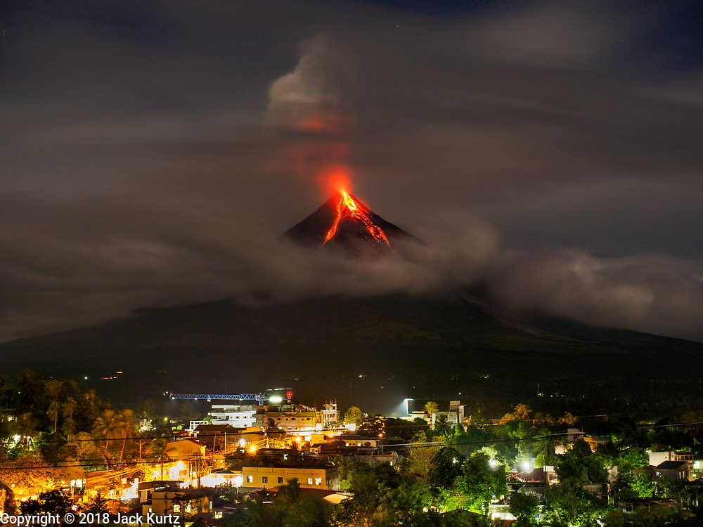 25 JANUARY 2018 - DARAGA, ALBAY, PHILIPPINES:  The Mayon volcano erupts Thursday night with the town of Daraga in the foreground. The Mayon volcano continued to erupt Thursday. The airport in Legazpi is closed until at least 31 January 2018. More than 60,000 people have been evacuated because of the volcano.    PHOTO BY JACK KURTZ