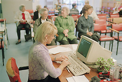 Receptionist working on computer in waiting room of Fracture Clinic in hospital,