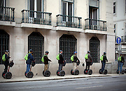 A group of tourists on an organized Segway tour, at Rua da Alfândega, downtown Lisbon.This photograph is part of a body of work about Lisbon, feelings, affections and loneliness. Is about a city depressed by the crisis, but even so, tolerant and cosmopolitan. This part of Lisbon, the old town near the river Tejo (Tagus), with his deep character, where local people meets foreigners and alternative ways of life mixes with shamefaced poverty, is sublime by its peculiar light.