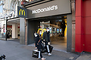 People wearing face masks pass McDonalds, which is now closed as a sit down fast food restaurant, but still open for take away orders on Oxford Street, Londons main shopping and retail area normally full of thousands of shoppers and traffic is virtually deserted due to the Coronavirus outbreak on 23rd March 2020 in London, England, United Kingdom. Following government advice most shoppers are staying at home leaving the streets quiet, empty and eerie. Coronavirus or Covid-19 is a new respiratory illness that has not previously been seen in humans. While much or Europe has been placed into lockdown, the UK government has announced more stringent rules as part of their long term strategy, and in particular social distancing.