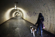 Woman walking her dog in a tunnel for pedestrians connecting the Prague quaters Zizkov and Karlin.