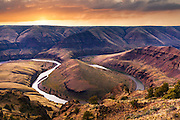 Sunset light casts a warm glow over a horseshoe shaped bend of Oregon's John Day River, as it winds its way northward to the mighty Columbia.