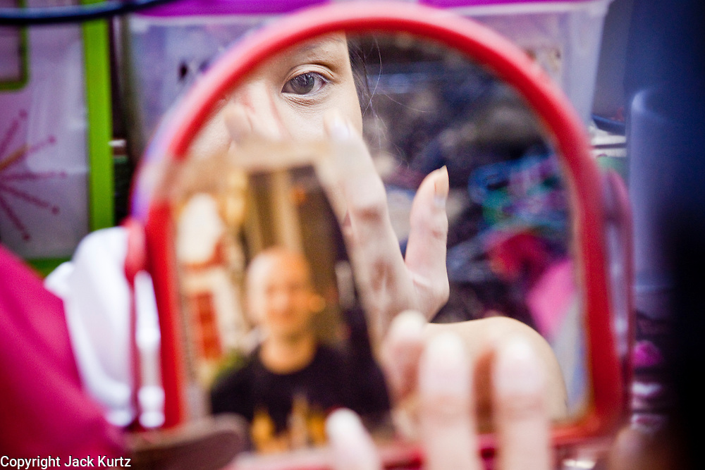 """Oct. 7, 2009 -- BANGKOK, THAILAND:  A """"Ladyboy"""" puts on her makeup in front of a mirror with a picture of her European boyfriend at the Mambo Cabaret. The performers at the Mambo Cabaret in Bangkok, Thailand are all """"Ladyboys,"""" or kathoeys in Thai. Recognized as a third gender, between male and female they are born biologically male but live their lives as women. They frequently undergo gender reassignment surgery to become women. Being a kathoey in Thailand does not carry the same negative connotation that being a transgendered person in the West does. A number of prominent Thai entertainers are kathoeys. Kathoeys frequently work in Thailand's sex trade and many times have long term relationships with European men who come to Thailand as tourists.     Photo by Jack Kurtz / ZUMA Press"""