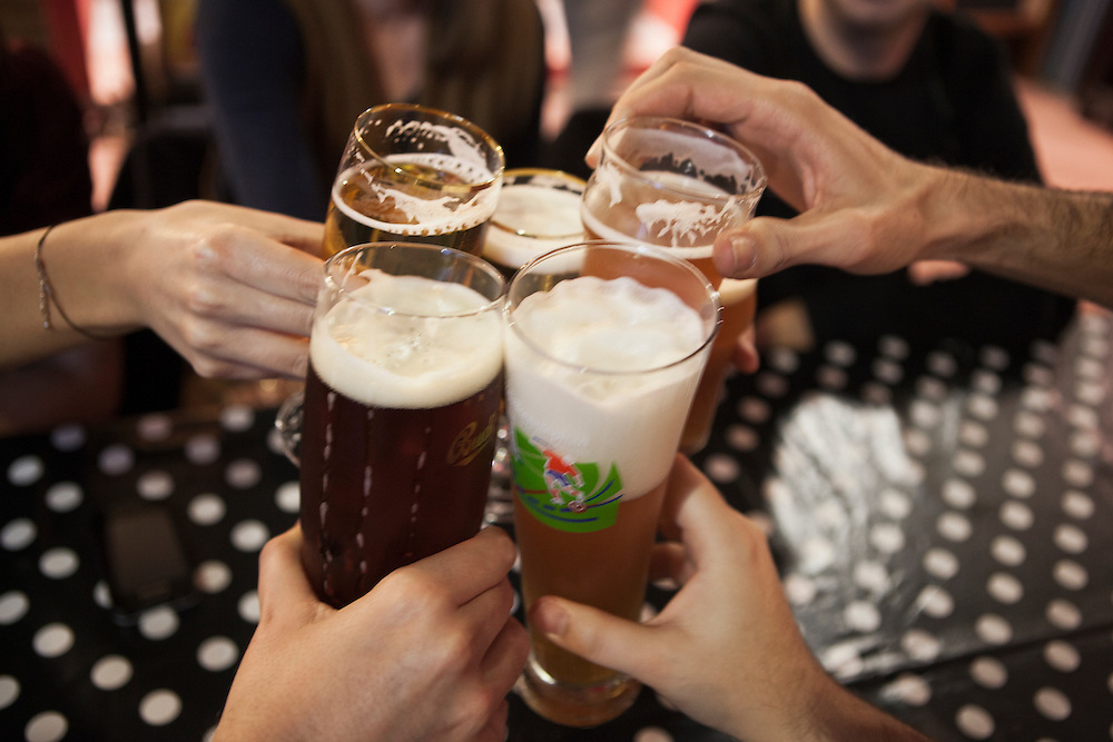 Patrons toasting with beer at La Cervecita Nuestra de Cada día, a boutique that serves only artisan-made beers, in the Poblenou neighbourhood of, Barcelona, Catalonia, Spain.