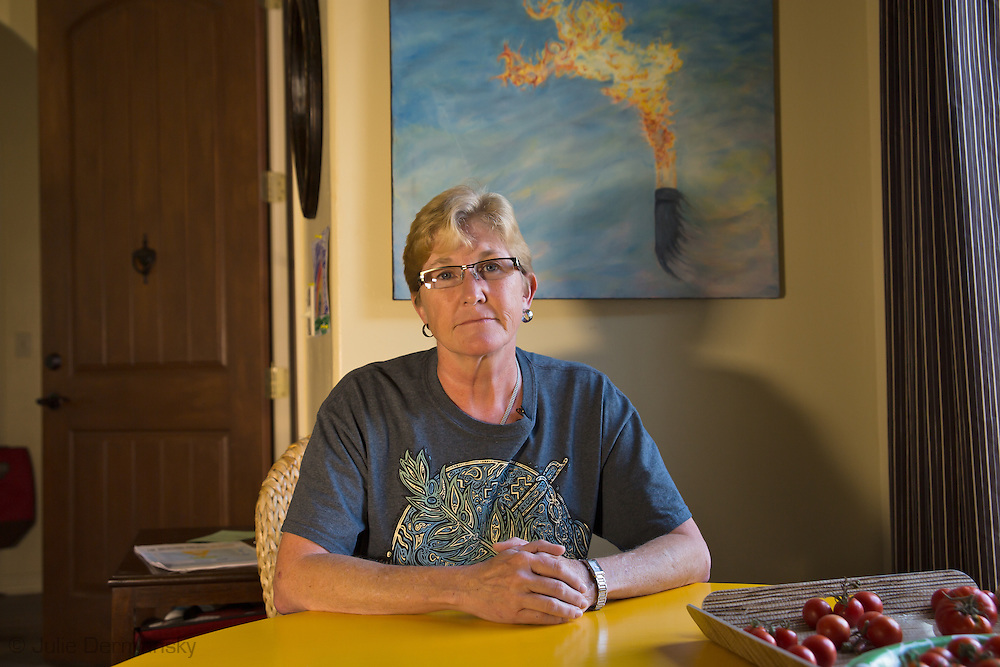 Anti-fracking  Oklahoma activist Angela Spotts at her home on the outskirts of Stillwater, OKlahoma with a painting of a flare behind her. .