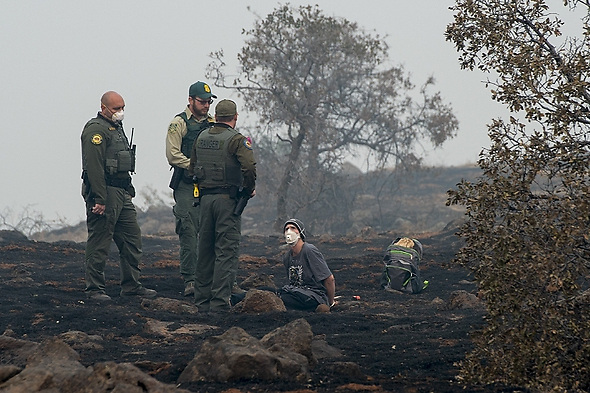 """November 15, 2018 - Paradise, California, U.S.: Arrested for trying going home! Paradise resident, CHARLIE MILES, 27, was sitting cross legged on the ground in handcuffs, with state rangers around him, after being arrested for trying to go home, Thursday. Miles, was on a desolate stretch of Skyway Road about halfway between his family's home, in the devastated town of Paradise and the church shelter in Chico, where he has been sleeping on a cot. His crime was trying to go back home. Miles was trying to see if anything was left of his and his parents trailers. Miles rose on the morning of Nov. 8 at 5:45 am. """"I had coffee with my parents like I always do,"""" he said. """"Then I was brushing my teeth and I looked up at the sky and it was gray. At that point, I started packing their stuff."""" The flames soon chased them. """"I was forced to drag everyone off the property,"""" he said. """"My dad was helping my mom and I was carrying their belongings. There were trees exploding. People were trying to drive their cars out but they couldn't. We have lost absolutely everything we owned,"""" The officers drove him back to the Chico City limits and set him free. """"They didn't give me a ticket or anything,"""" Miles said. He said a friend was able to return to their street and told him, everything is gone. Miles and his parents are but one of scores of victims of the deadliest wildfire in California history, the Camp Fire started Nov. 8th at crack of dawn, its death toll grew today to 77, while the number of people unaccounted is over thousand people. The blaze is now, two-thirds contained, after consuming some 150,000 acres. (Credit Image: © Renee C. Byer/Sacramento Bee via ZUMA Wire)"""