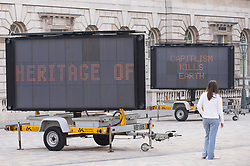 "© Licensed to London News Pictures. 16/04/2019. LONDON, UK. Gallery staff pose with ""REDUCE SPEED NOW!"" by American artist Justin Brice Guariglia, a major courtyard installation at Somerset House launching Earth Day Season, a fortnight of installations and events exploring creative responses to climate change.  Formed of nine large solar-powered LED signs usually seen on motorways, the installation brings together the critical voices of international activists, poets and philosophers to address the global ecological crisis..  Photo credit: Stephen Chung/LNP"