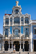 Tourists pass ornate Museu Arte Nova - Modern Art Museum and Casa de Cha with traditional balconies - in Aveiro, Portugal