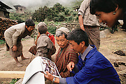 Shingkhey villagers (Uncle Kinley Dorji at center) look at images of other countries from the Material World Project. Bhutan. The family of subsistence farmers lives in a 3-story rammed-earth house in the hillside village of Shingkhey, Bhutan.