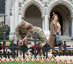 © Licensed to London News Pictures. 05/11/2014. London, UK. Lance Sergeant French and Guardsman Legg of the Scots Guards plant wooden poppy crosses in their  regiment's plot in the field which opens to the public tomorrow (Thursday 6th November) Every November the annual Field of Remembrance at Westminster Abbey is organised and run by The Poppy Factory. Over 350 plots for regimental and other associations are laid out in the area between Westminster Abbey and St. Margaret's Church. Remembrance crosses are provided so that ex-Service men and women, as well as members of the public, can plant a cross in memory of their fallen comrades and loved ones.<br /> . Photo credit : Stephen Simpson/LNP