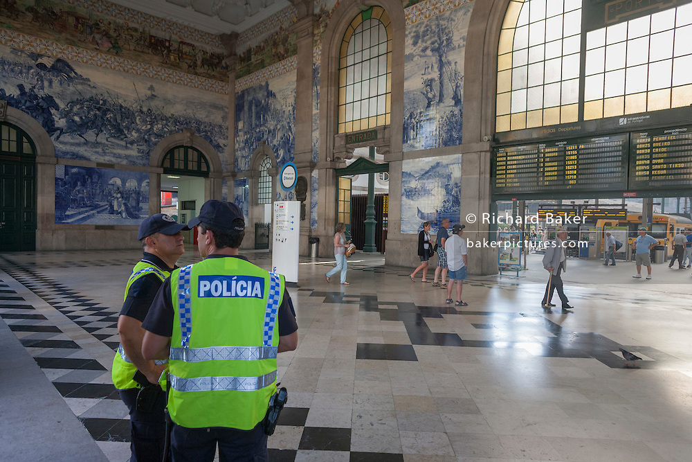 Police officers keep watch beneath traditional Azulejo tiles inside the ornate Sao Bento railway station in Port, Portugal.