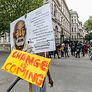 A demonstrator points at a banner during a rally at Downing Street in London, Tuesday, June 9, 2020. Anger against systemic levels of institutional racism has raged through the city, and worldwide; sparked by the death of George Floyd, who was killed in Minneapolis, US, by a policeman who restrained him with force on 25 May 2020. (Photo/ Vudi Xhymshiti)