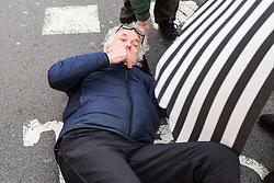 PICTURED: A protester lies on the road after being clipped by a passing cyclist. Demonstrators from the anti-pollution group Stop Killing Londoners cause traffic chaos for London commuters as they conduct a series of short roadblocks at Marble Arch stopping cars and buses from entering Oxford Street and Park Lane. Irate motorists accused them of creating more pollution than they were stopping, whilst the group said their objectives were long term. A leaflet handed out to motorists says the government is not doing enough to tackle the crisis costing 'taxpayers and the NHS £billions [sic] a year'. PLACE, January 29 2018. © Paul Davey