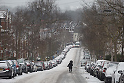 A person crosses an icy minor road in the south London borough of Herne Hill, Lambeth during the bad weather covering every part of the UK and known as the Beast from the East because Siberian winds and very low temperatures have blown across western Europe from Russia, on 1st March 2018, in Lambeth, London, England.