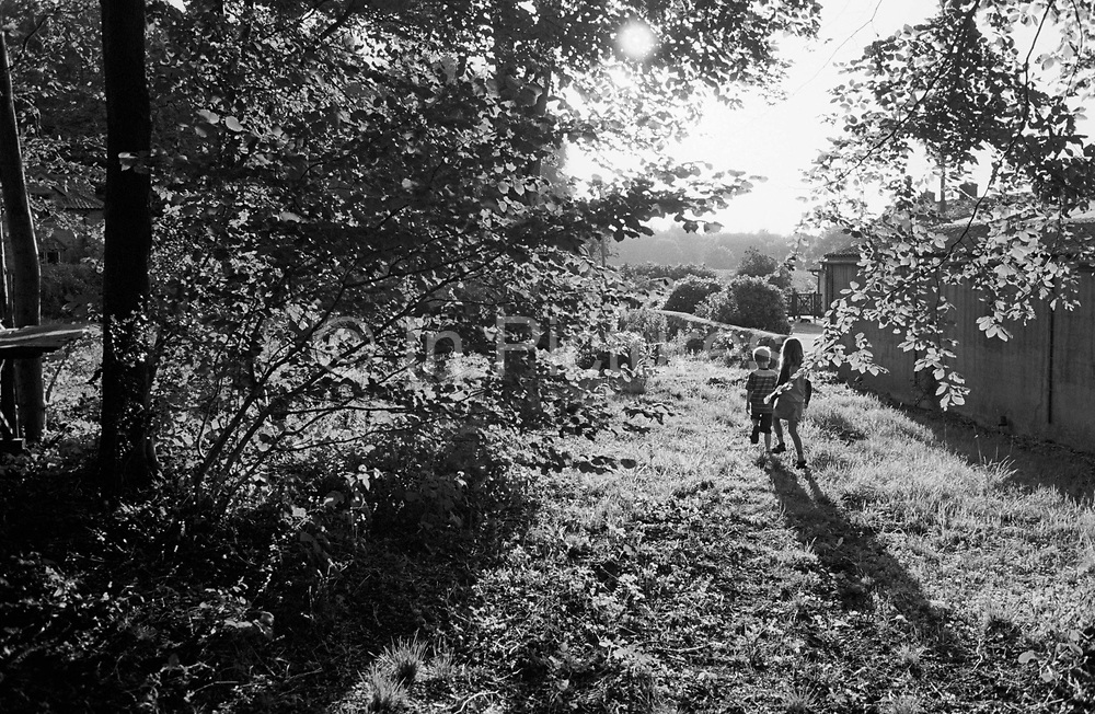 """Two young children experience a little independence during a walk by themselves through a wood near their grandparents' cottage in Somerset, England. Discovering for themselves the delights of childish adventure without the worries of security unfortunately prevalent in the inner-cities. Here in the forest they return home with the sun in their eyes having had the time of their lives. The beech trees' branches are full with leaves on this mid-summer afternoon in this tranquil scene of childhood innocence, of long summer days and summer holidays. From a personal documentary project entitled """"Next of Kin"""" about the photographer's two children's early years spent in parallel universes. Model released."""