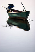 Koh Kut, Thailand - A small boat moored in calm water with a clear reflection.