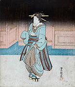 Geisha on an evening stroll in Fukagawa, c1830.  Utagawa Toyokuni (c1777-1835) Japanese Ukiyo-e artist. Geisha with traditional hairstyle in blue kimono, wearing pattens, holding robe to avoid ground.  Entertainer Female