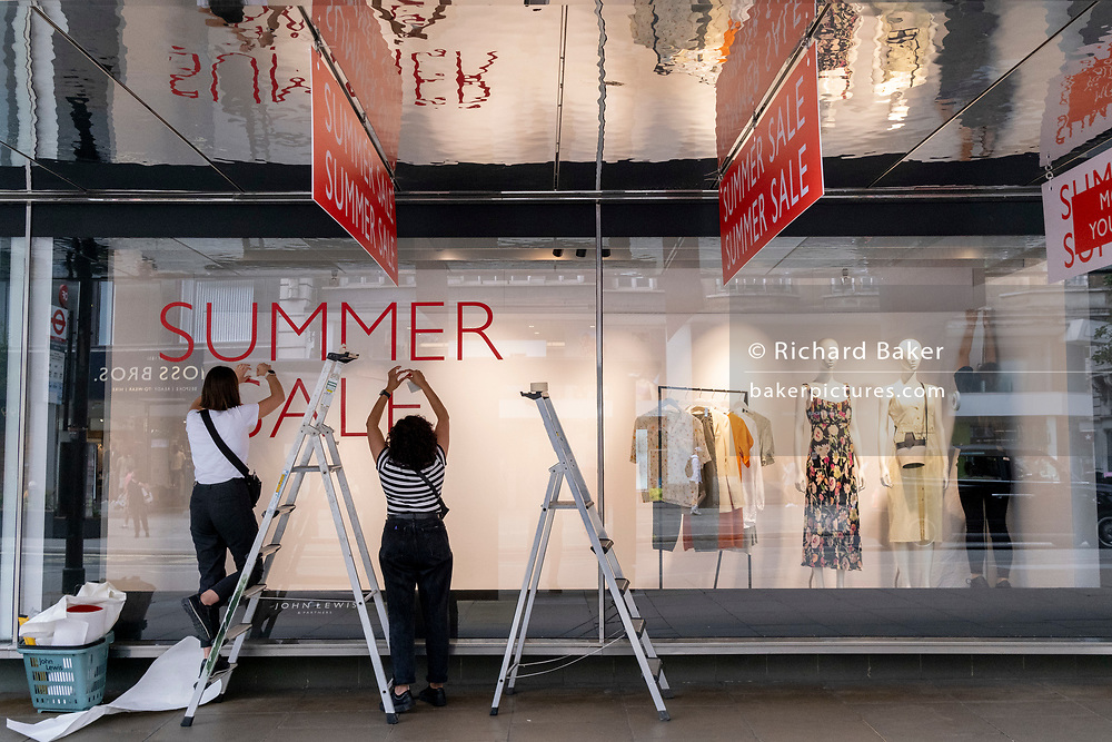 Staff from High Street retailer John Lewis attatch sticky transfers for the upcoming John Lewis Summer Sale on Oxford Street, on 5th July 2021, in London, England.