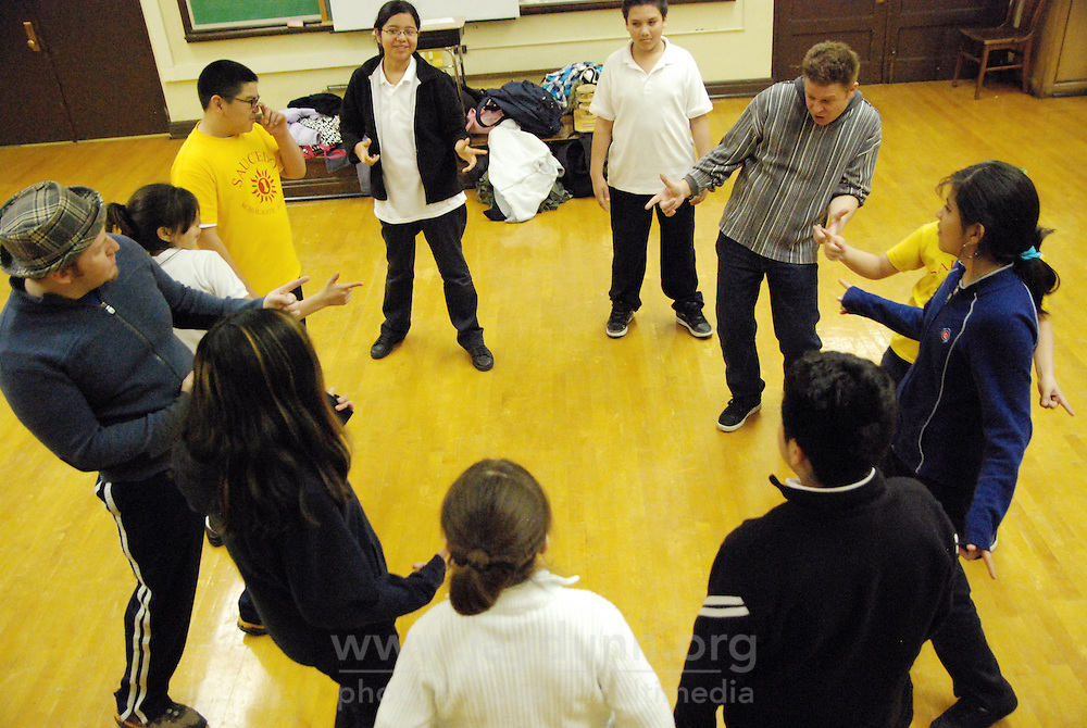 """USA, Chicago, IL, December 12, 2009.  Working as a team and following instruction are taught in class. Students in the """"At-Risk After School Program"""" at Maria Saucedo Scholastic Academy receive training in basic physics principles through an innovative new program called """"Circus Galactica"""" put on by Pros Arts, a non-profit organization founded in 1978 by professional artists dedicated to the Pilsen/Little Village communities. In a residency that directly integrates science and art, veteran circus performers Douglas Grew and Paul Lopez bring the importance of """"balance, focus and presentation"""" into hands-on lessons about gravity, inertia, and the dynamics of objects in motion. Photo for Hoy by Jay Dunn."""