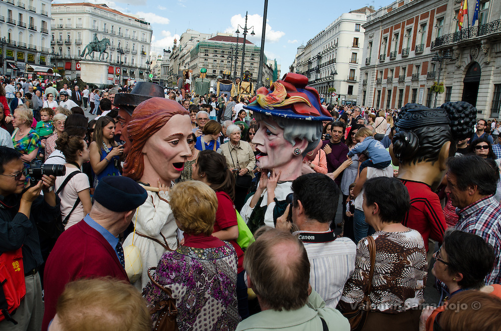 People talking with Cabezudos from Madrid during San Isidro 2013 parade.