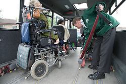 Driver of mini bus securing wheelchairs ready for transporting,