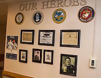 Belknap County Nursing Home's Veteran's wall with photos of John Neylon U.S. Marines,  Dana Aloise U.S. Army and Sheldon MacKnight U.S. Navy taken during their years of service in the United States Military.  (Karen Bobotas/for the Laconia Daily Sun)