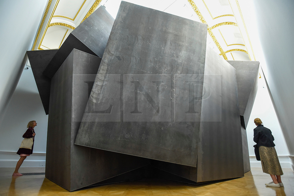 """© Licensed to London News Pictures. 17/09/2019. LONDON, UK. Visitors outside """"Cave"""", 2019, by Antony Gormley, 27 tonnes of weathering steel. Preview of a new exhibition by Antony Gormley at the Royal Academy of Arts.  The show bring together existing and specially conceived new works from drawing to sculptures to experimental environments to be displayed in all 13 rooms of the RA's Main Galleries 21 September to 3 December 2019.  Photo credit: Stephen Chung/LNP"""