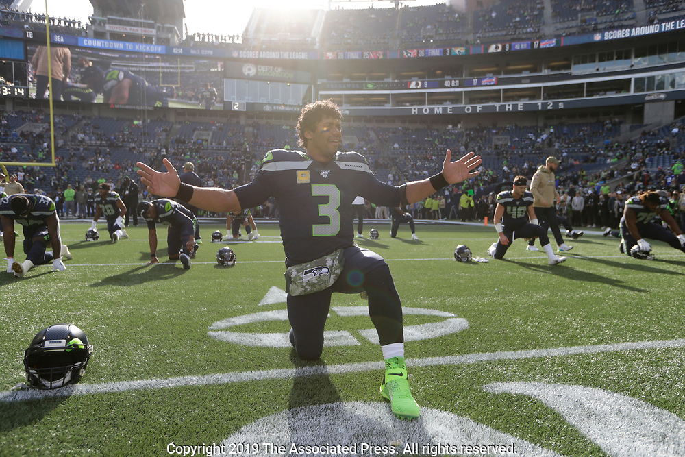 Seattle Seahawks quarterback Russell Wilson reacts in the sunshine as he stretches before an NFL football game against the Tampa Bay Buccaneers, Sunday, Nov. 3, 2019, in Seattle. (AP Photo/John Froschauer)