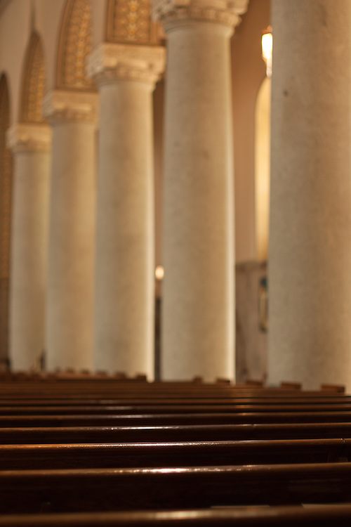 Marble pillars and wooden pews in a chapel.