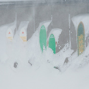 Old skis screwed to the walls of Corbet's Cabin covered in blowing winter storm snow.