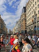 Pedestrians crossing busy road of Gran Via, Madrid city centre, Spain