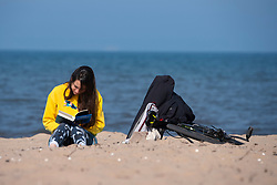 Portobello, Scotland, UK. 25 April 2020. Views of people outdoors on Saturday afternoon on the beach and promenade at Portobello, Edinburgh. Good weather has brought more people outdoors walking and cycling. The beach appears busy with possibly a breakdown in social distancing happening later in the afternoon. Solitary woman reading book on the beach. Iain Masterton/Alamy Live News