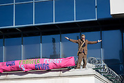 An environmental activist on the roof protests about Climate Change during the occupation of City Airport Londons Business Travel hub in east London, the fourth day of a two-week prolonged worldwide protest by members of Extinction Rebellion, on 10th October 2019, in London, England.