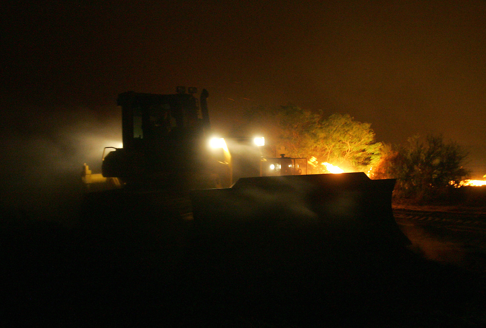 San Manuel, TX - 18 Mar 2008 -.A City of McAllen bulldozer cuts a fire break along US 281 north of San Manuel to control a large fire on Tuesday night..Photo by Alex Jones / ajones@themonitor.com