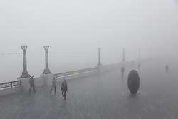 © Licensed to London News Pictures. 13/03/2014. London, UK. People walk on the Thames path near Tower Bridge during thick fog in London this morning, 13th March 2014. Photo credit : Vickie Flores/LNP