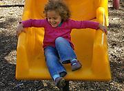 Bi-racial Child on Urban Playground Sliding Board, Joyous