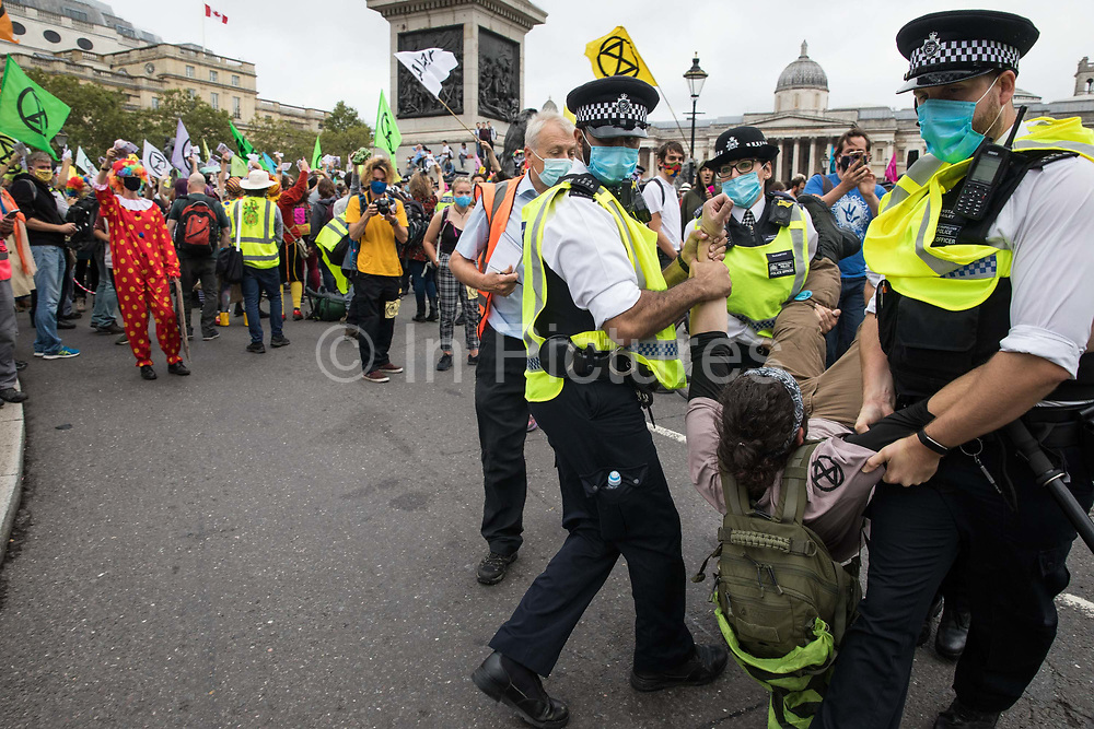 Metropolitan Police officers arrest a climate activist from Extinction Rebellion in Trafalgar Square during a 'Carnival of Corruption' protest against the government's facilitation and funding of the fossil fuel industry on 3 September 2020 in London, United Kingdom. Extinction Rebellion activists are attending a series of September Rebellion protests around the UK to call on politicians to back the Climate and Ecological Emergency Bill CEE Bill which requires, among other measures, a serious plan to deal with the UK's share of emissions and to halt critical rises in global temperatures and for ordinary people to be involved in future environmental planning by means of a Citizens' Assembly.