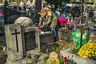 A woman lights a candle at Rakowicki cemetery in Krakow, Poland 2019.