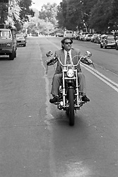 man wearing a suit while driving a motorcycle in New York City