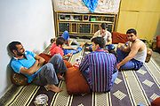 A young group of local residents who helps the revolution and stand by the Democratic Values along with the Free Syrian Army armed fellow residents are seen gathered whilst playing cards together in a house where the members of the Free Syrian Army, live and maintain the security of Marea on the early morning of Wednesday, June 27, 2012. (Photo by Vudi Xhymshiti)