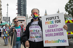 Peter Tatchell, veteran LGBTI+ and human rights campaigner, poses with a placard in Parliament Square before the first-ever Reclaim Pride march on 24th July 2021 in London, United Kingdom. Reclaim Pride replaced the traditional Pride in London march, which many feel has become too commercial and strayed from its roots in protest, and was billed as a People's Pride march for LGBTI+ liberation. Campaigners called for the banning of LGBTI+ conversion therapy, the reform of the Gender Recognition Act, the provision of a safe haven for LGBTI+ refugees and for LGBTI+ people to be decriminalised worldwide and marched in solidarity with Black Lives Matter.