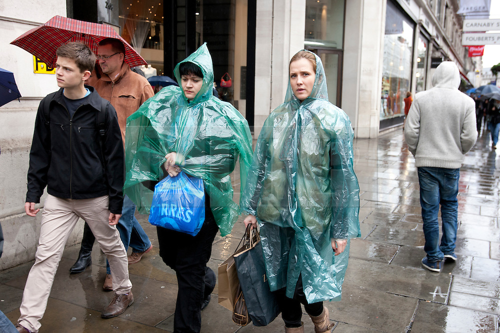 © licensed to London News Pictures. London, UK 09/04/2012. People walking on Regents Street with raincoats and umbrellas as they face rain and wind in central London, this afternoon (09/04/12). Photo credit: Tolga Akmen/LNP