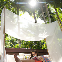 Relaxing in a day bed under palms at the luxurious Molori retreat in Port Douglas, Queensland, Australia.