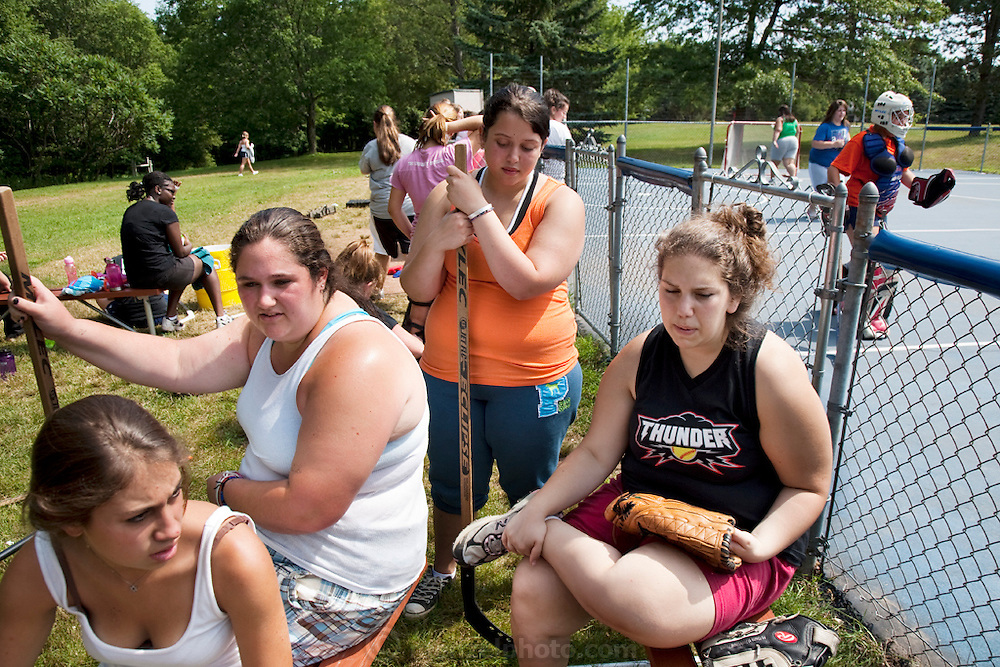 Mackenzie Wolfson, a natural athlete (second from left) and accomplished tennis player and a member of her school's varsity softball team, takes a break on the sidelines of a field hockey game on a hot afternoon with her teammates at Camp Shane, Catskill Mountains, New York.  (From the book What I Eat: Around the World in 80 Diets.) The caloric value of her typical day's worth of food in July was 1,700 kcals. She is 15; 5 feet nine inches tall,  and 299 pounds.