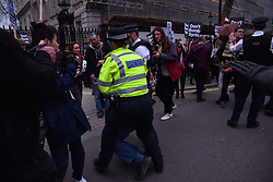April 13, 2018 - London, England, United Kingdom - Police Officers arrest a man during a protest outside the gates of Downing Street, against the British government's decision to attack Syria, London on April 13, 2018. Labour Party leader, Jeremy Corbyn, has accused Prime Minister Theresa May to 'wait for Trump' about wether to launch a missile attack on Syria. (Credit Image: © Alberto Pezzali/NurPhoto via ZUMA Press)