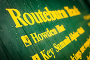 Green directional sign with yellow letters along Routeburn Track, South Island, New Zealand